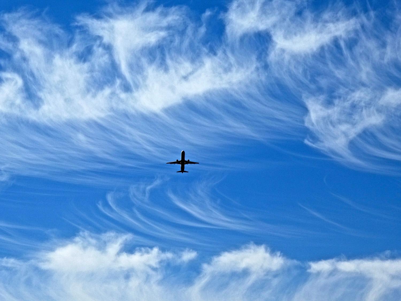 Een opstijgend vliegtuig tussen veegwolken boven de Grote Speelweide
