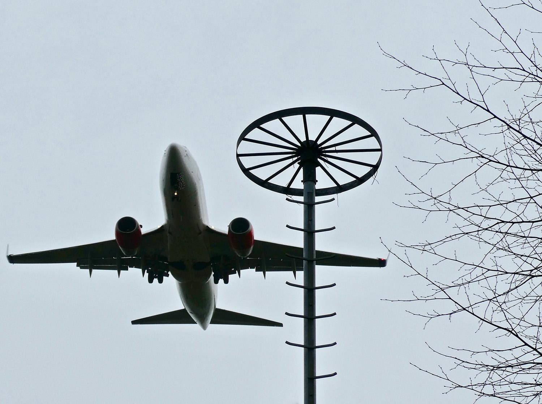 Een dalend vliegtuig trotseert de harde wind boven boerderij Meerzicht