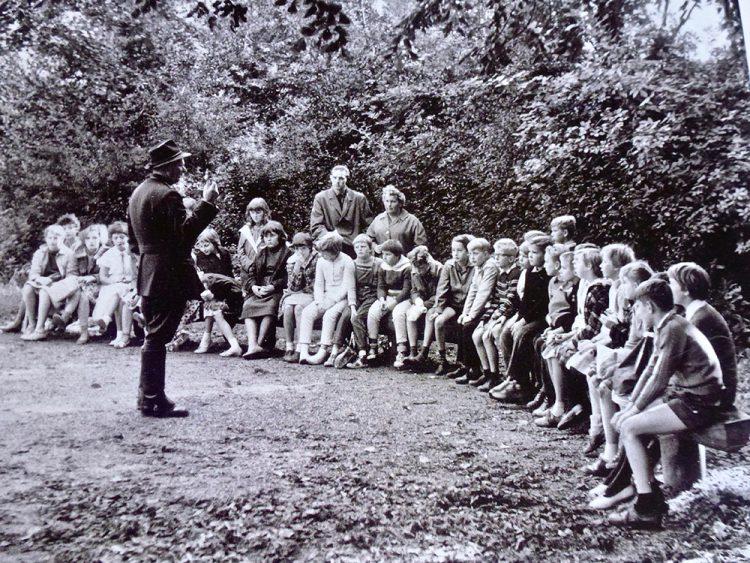 Boswachter Piet Brander vertelt een schoolklas over het Bos
